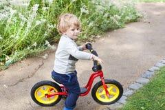 2岁在他的第一辆自行车的小孩骑马 免版税图库摄影
