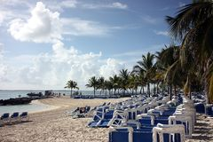 2把海滩岩礁椅子椰树休息室 图库摄影