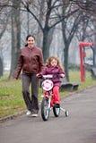 2辆自行车bycicle女孩小的母亲骑马 免版税库存照片