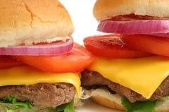 2 μεγάλες cheeseburgers upclose W εργασίες Στοκ Εικόνες
