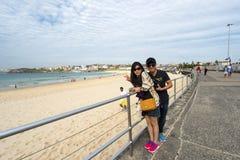 2 азиатских туриста на пляже Bondi Стоковое Фото