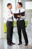2 бизнесмена имея неофициальное заседание в самомоднейшем офисе Стоковые Фотографии RF