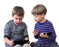 2 брать играя видеоигры на таблетках Стоковые Изображения