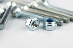 2 гайки металла на предпосылке металла скрепляют болтами Стоковое Изображение RF