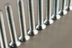 2 гайки металла на предпосылке металла скрепляют болтами Стоковые Изображения RF