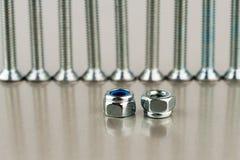 2 гайки металла против некоторых ровных болтов металла Стоковые Изображения RF