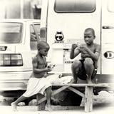 2 ганских дет сидят на стенде около ro Стоковые Изображения