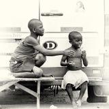 2 ганских дет сидят на стенде около ro Стоковые Фотографии RF