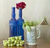 2 голубых бутылки, виноградины и травы Стоковые Фото