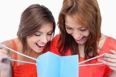 2 девочка-подростка смотрящ их покупкы Стоковые Изображения