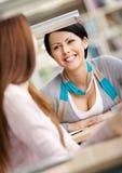 2 девушки говорят сидеть на столе Стоковое Изображение RF