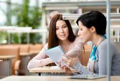 2 девушки говорят сидеть на таблице Стоковое Изображение
