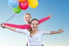 2 девушки играя снаружи с воздушными шарами Стоковые Фото