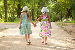 2 девушки идут рука - внутри - рука Стоковые Изображения RF