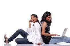 2 девушки используя компьтер-книжку и мобильный телефон Стоковое фото RF