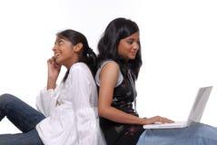 2 девушки используя компьтер-книжку и мобильный телефон Стоковое Изображение RF