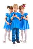 2 девушки и мальчик с их сотовыми телефонами Стоковая Фотография