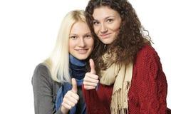 2 девушки показывая большой пец руки вверх по знакам Стоковые Изображения