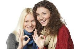 2 девушки показывая ОДОБРЕННЫЕ знаки Стоковые Изображения