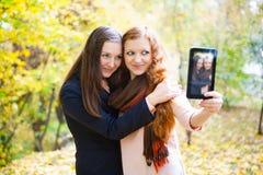 2 девушки принимая автопортрет в парке осени Стоковое Изображение