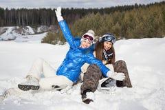 2 девушки сидя на снежке и смеяться над Стоковые Изображения