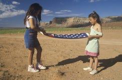 2 девушки складывая американский флаг, Стоковое фото RF
