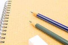 2 деревянный карандаш, истиратель на тетради. Стоковая Фотография
