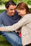 2 друз смотрят счастливо к земле по мере того как они сидят рядом с Стоковая Фотография