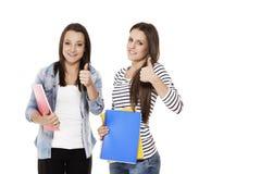 2 женских студента показывая большие пальцы руки вверх Стоковые Изображения