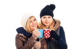 2 женщины в зиме одевают кружку удерживания Стоковые Фотографии RF