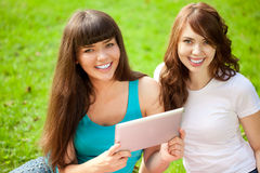 2 женщины в парке на пикнике с ПК таблетки Стоковые Изображения RF