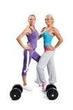 2 женщины мышцы представляя на белой предпосылке Стоковое Фото