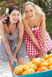 2 женщины нажимая тачку заполнили с померанцами Стоковое Изображение RF