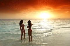 2 женщины наслаждаясь заходом солнца на пляже Стоковое фото RF
