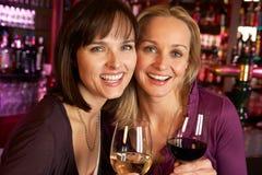 2 женщины наслаждаясь питьем совместно в штанге Стоковая Фотография RF