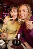 2 женщины наслаждаясь сушами в ресторане Стоковые Фотографии RF