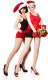 2 женщины нося шлемы santa имеют потеху Стоковые Изображения