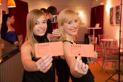 2 женщины представляя билеты театра или кино Стоковая Фотография RF