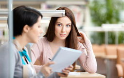 2 женщины связывают сидеть на столе Стоковые Фотографии RF