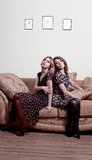 2 женщины сидя назад к задней части Стоковые Фото