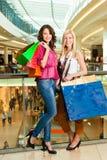 2 женщины ходя по магазинам с мешками в моле Стоковое фото RF