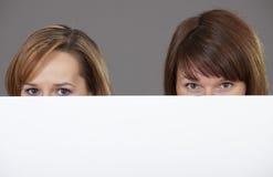 2 женщины peeking над белым знаменем Стоковые Фотографии RF