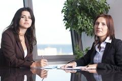 2 коммерсантки сидя на столе офиса Стоковые Фото