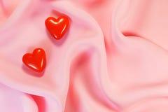 2 красных сердца на шелке Стоковое Изображение