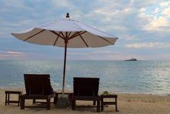 2 кровати и зонтик на пляже на заходе солнца Стоковое Изображение
