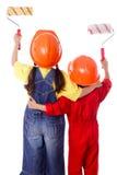 2 малыша в coveralls с роликами краски стоковое изображение