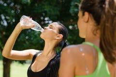 2 молодой женщины ослабляя после пригодности в парке Стоковое Фото