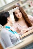 2 молодой женщины связывают сидеть на столе Стоковые Фото