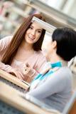 2 молодой женщины связывают сидеть на таблице Стоковая Фотография RF