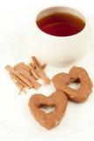 2 печенья, чашка с чаем и ручки циннамона Стоковая Фотография